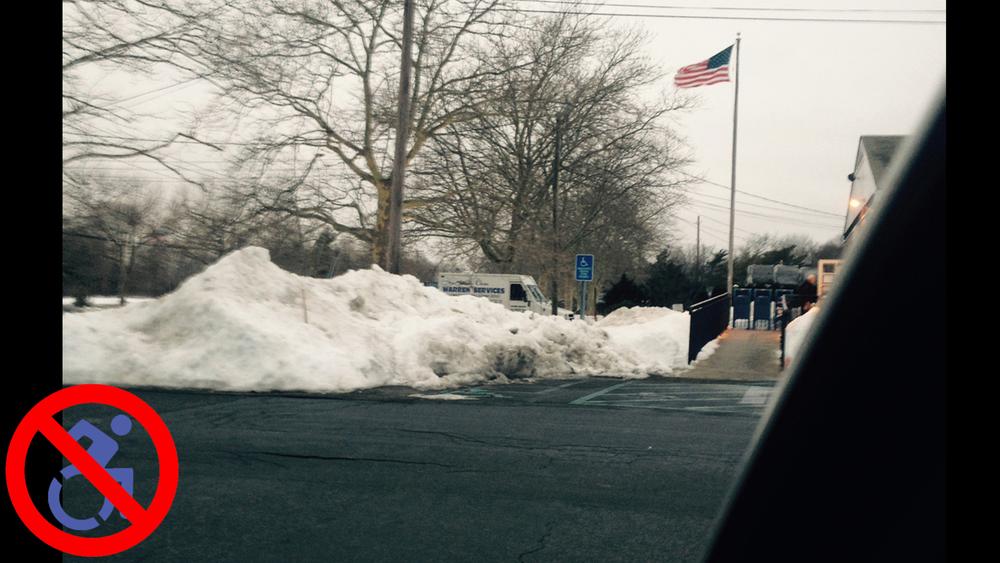 Snow blocking a handicap parking spot.