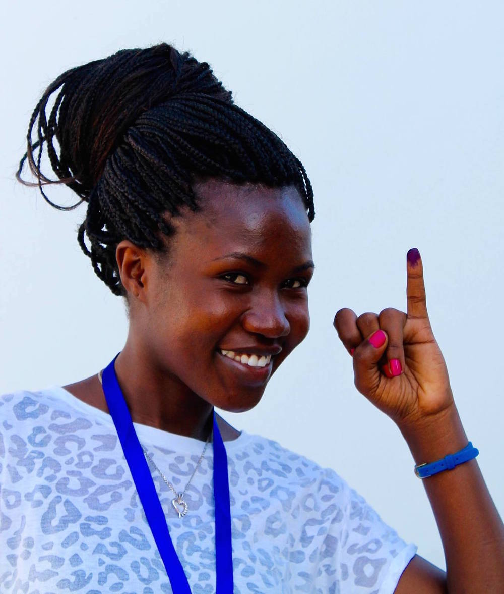 A data clerk for the Tanzania Youth Coalition youth observation program proudly displays her inked finger after voting today in Tanzania's general election.