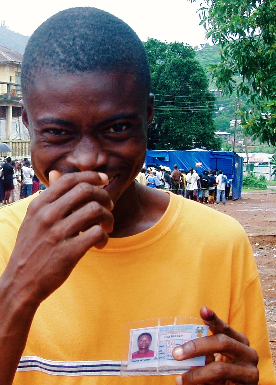 B.H. holds up his voter ID card on election day in Freetown