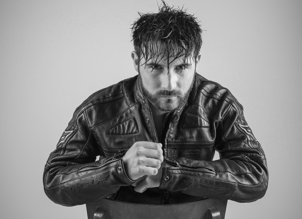 Male model in black and white black leather jacket sitting pose photo shoot in Hassocks venue Adastra Hall