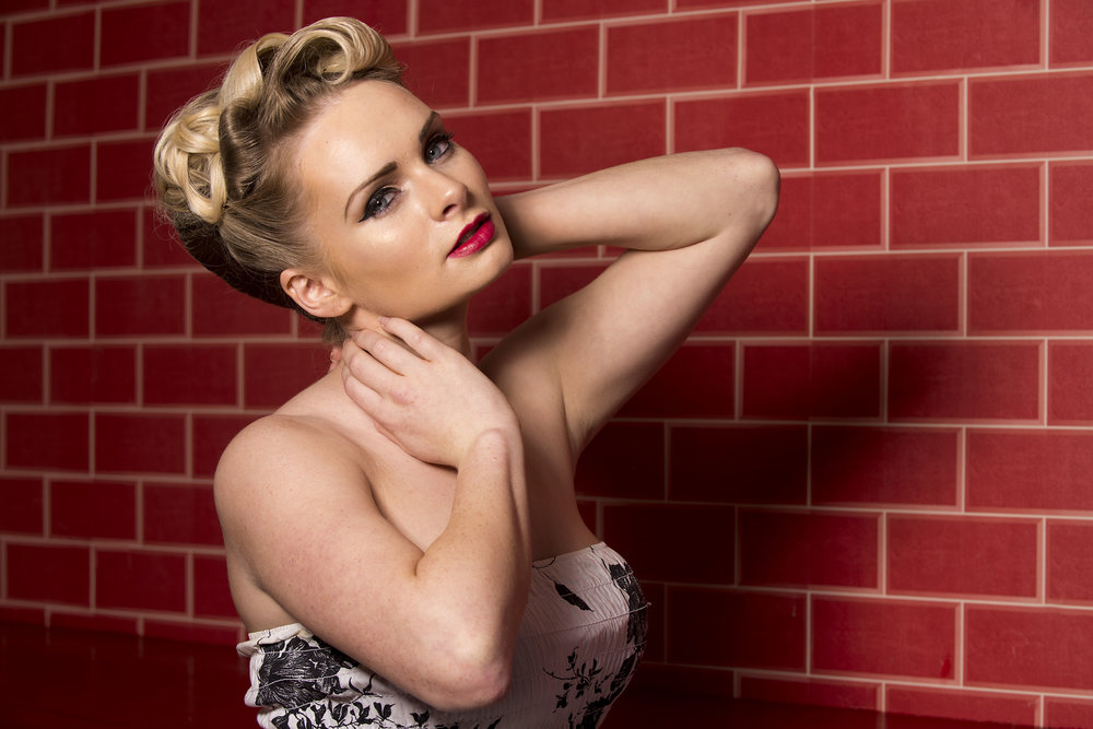 Blonde girl model close up pose red brick wall in Essex photographic studio
