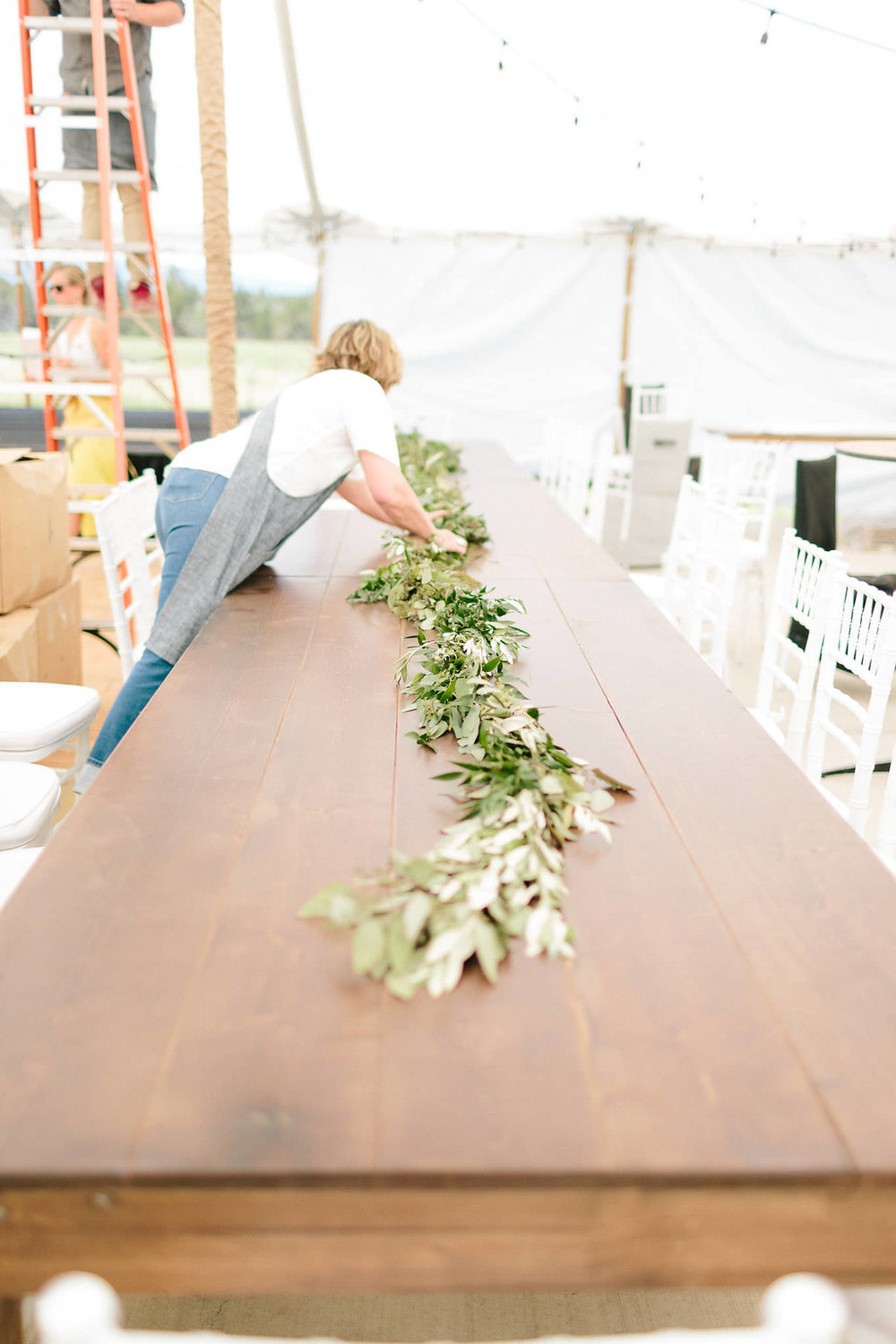 The farm tables were decorated with garlands of greenery and flowers that extended their length.