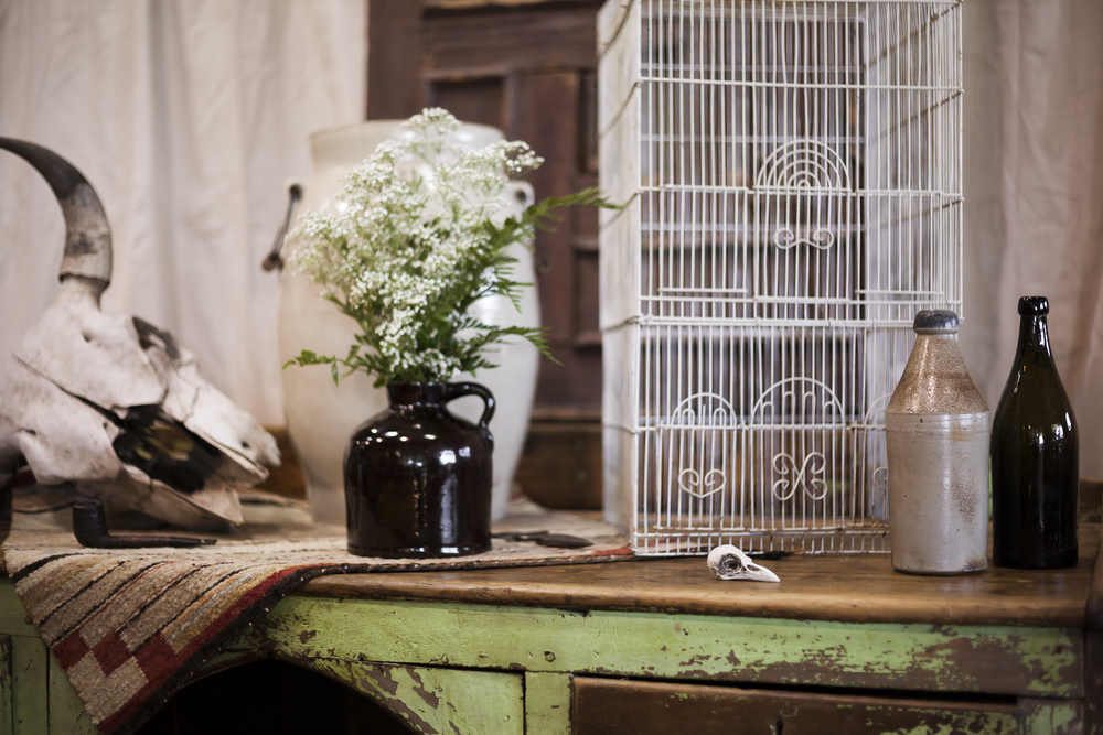 Distressed Table with Antique Milk Bottles, Birdcage, Table Cover and Skull