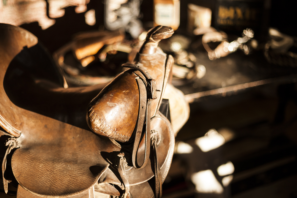 Antique Horse's Saddle in front of a Rustic Work Table