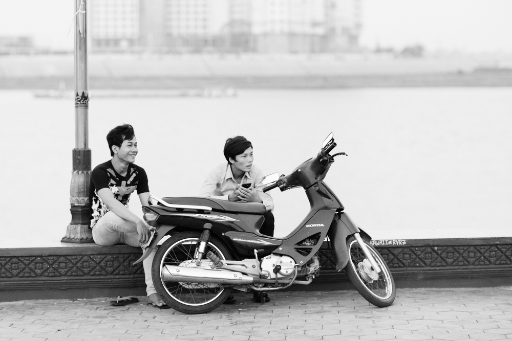A couple of Khmer kids and their motorbike hang out near the Tonle Sap River in Phenom Penh. Cambodia. March 2014.
