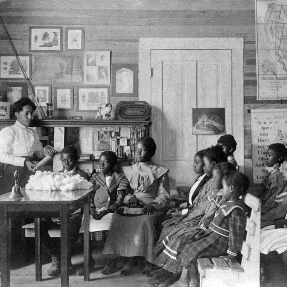 Frances Benjamin Johnston - African American children and teacher in classroom studying corn and cotton, Annie Davis School, near Tuskegee, Alabama, 1902.jpg