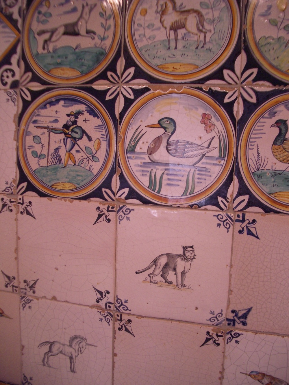 Delftware Tiles.  Behind the kitchen Wolf range is a panel of reproduction early and mid-seventeenth century Dutch tiles, some depict soldiers and animals set within borders of concentric circles,  others are mid-seventeenth century Dutch animal tiles with ox-head corner motifs and plain tiles with   flour-de-lis   corner motifs.  The corner motifs are executed in the reserving technique (such that when four corners meet, they create  an ornamental design).