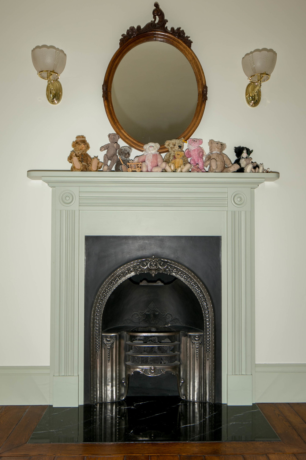 "An antique Victorian  cast iron ""hob grate"" which has been adapted to burn ceramic (reproduction) coal with a gas flame controlled by a wall switch.  The floors throughout are solid, hand-scraped, imported European coppice oak. The mantle is flanked by two Victorian reproduction gaslight fixtures from Roy Electric Lighting. Their lighting  can be seen at the White House Executive Building, U.S. Capitol Building in Washington, D.C., and Disney Worldwide."