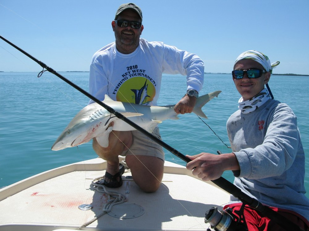 Mike Scherf and I with a blacknose shark like the one in the video below. Note that I am wearing shoes that protect my toes and I've got control of the shark by the midsection and tail.