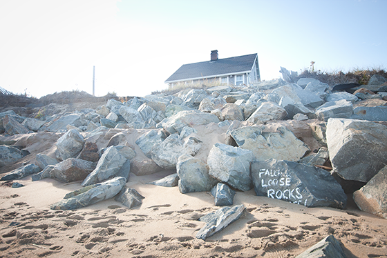 A rock wall intended to protect this Plum Island home has been heavily damaged by an unrelenting sea. (Rachel Playe/ecoRI News)