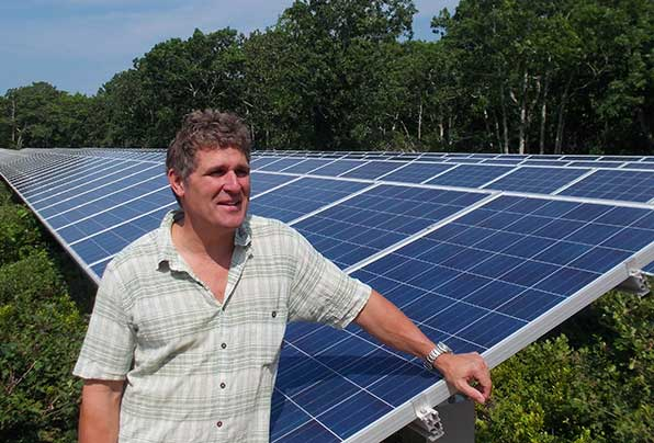 Developer Bill Bennett stands next to a solar field in Edgartown that provides renewable energy to local nonprofits. (Tim Faulkner/ecoRI News)