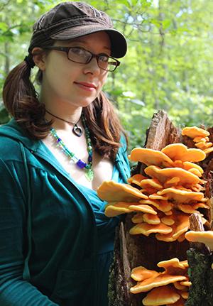 Emily Schmidt with an orange-and-yellow sun fungus. (Ryan Bouchard)
