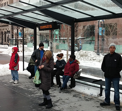 Riders wait at a new Kennedy Plaza bus stop. A sign offering real-time bus information is included at each new shelter in the plaza.