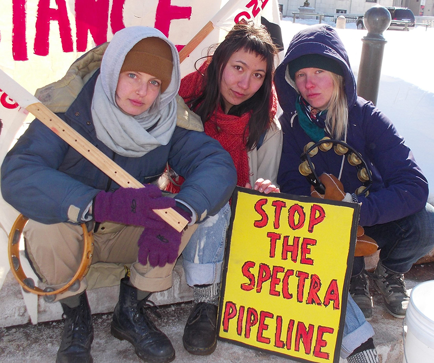 Anya Klepacki, left, Claire Sowa, middle, and Nelli Routsalainen of Stop the West Roxbury Lateral Pipeline outside the Rhode Island Statehouse during a March 6 protest. (Tim Faulkner/ecoRI News)
