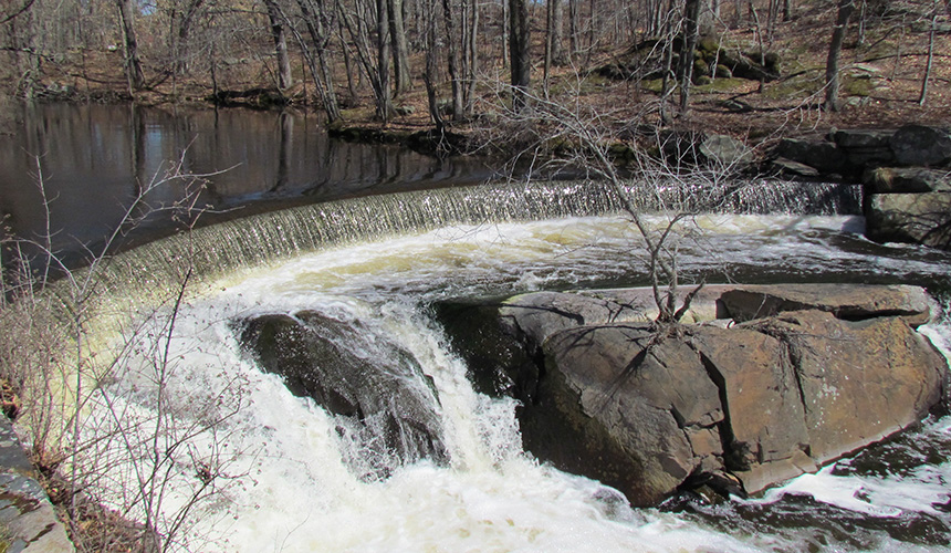 A pipe running between two dams on Ten Mile River in East Providence could reactivate the dormant Hunt's Mills hydropower facility, thanks to Rhode Island's distributed generation program. (Tim Faulkner/ecoRI News)