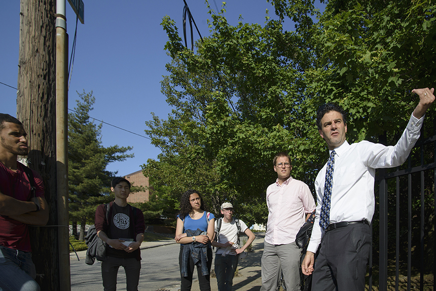 Providence City Council member Bryan Principe, right, and transit advocate James Kennedy, second from right, recently spoke with a small group of local college students, at the intersection of Marvin Street and Service Road 1, about the outdated 6-10 Connector across the street.