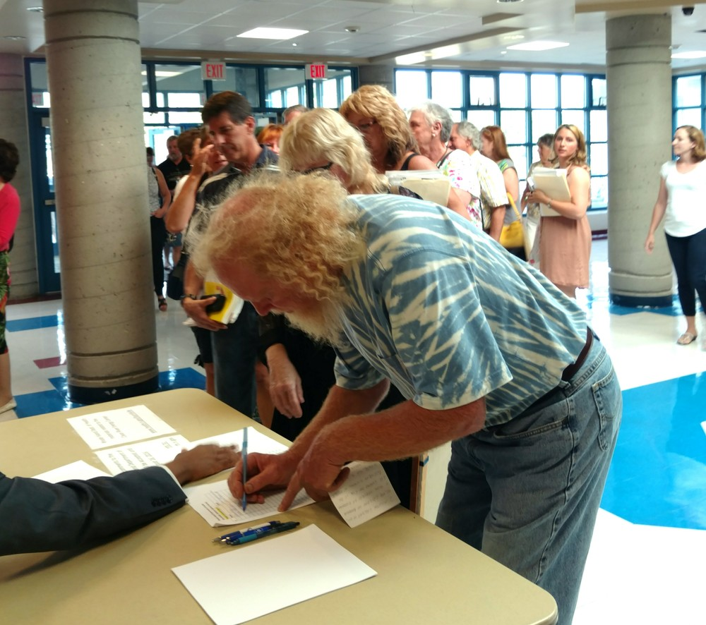All 34 speakers at an Aug. 9 public hearing spoke against the proposed fossil-fuel power plant. The public signed up outside the Burrillville High School auditorium to make statements. (Tim Faulkner/ecoRI News)