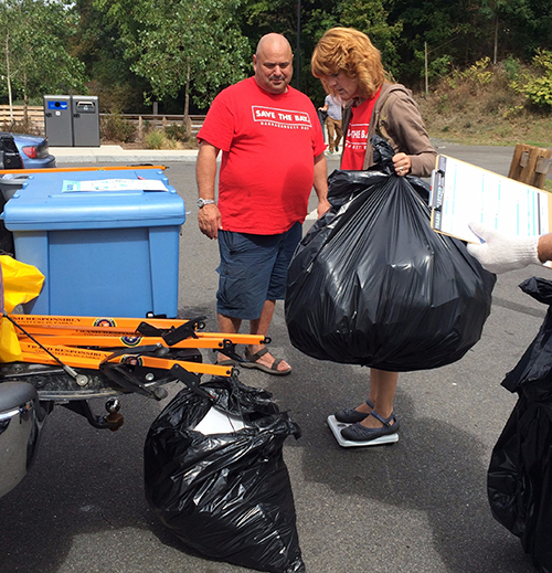 Dave Henault and Bonnie Combs weigh trash collected at Festival Pier in Pawtucket.