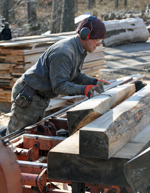 Rob Swanson moves trimmed logs onto the carriage of the sawmill in preparation for the final cuts into boards.