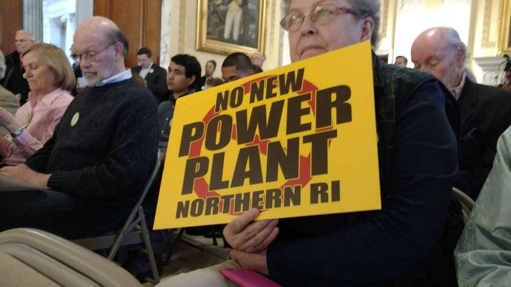 Opponents of the proposed Burrillville power plant held signs as Gov. Gina Raimondo spoke during the recent Lobby Day at the Rhode Island Statehouse. (Margaret Faulkner/ecoRI News)