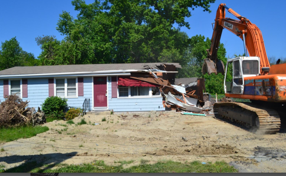 A home in a flood-prone neighborhood of Cranston, R.I., was bought by the city and torn down. The lot returned to shrubs and tall grasses to help reduce flooding. (city of Cranston photos)