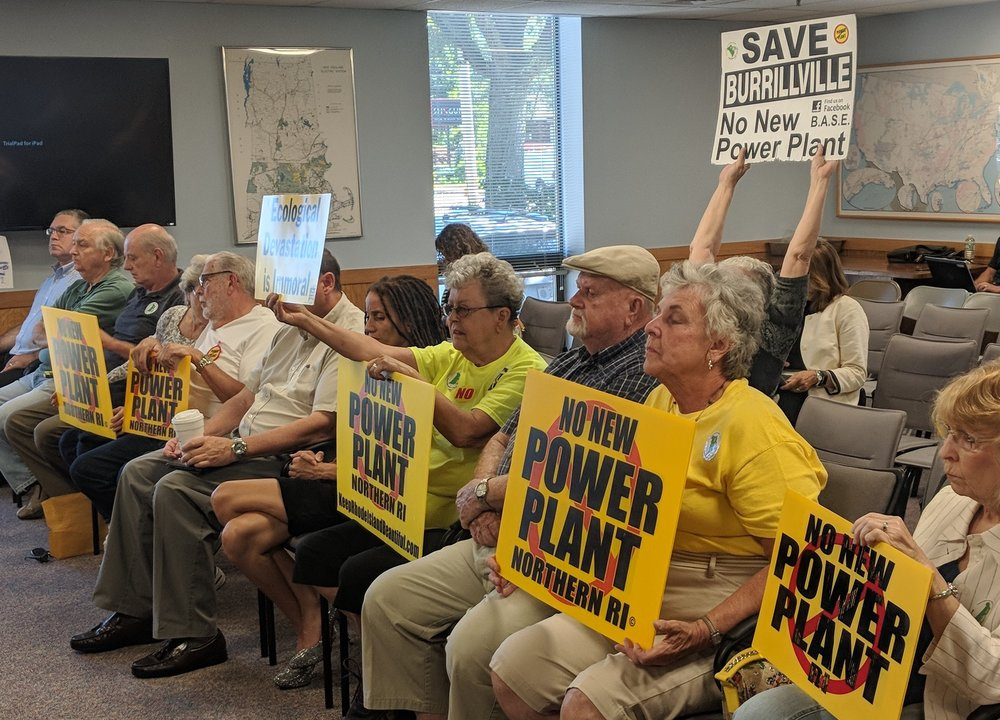Project opponents held signs during the recent Rhode Island Energy Facilities Siting Board meeting.