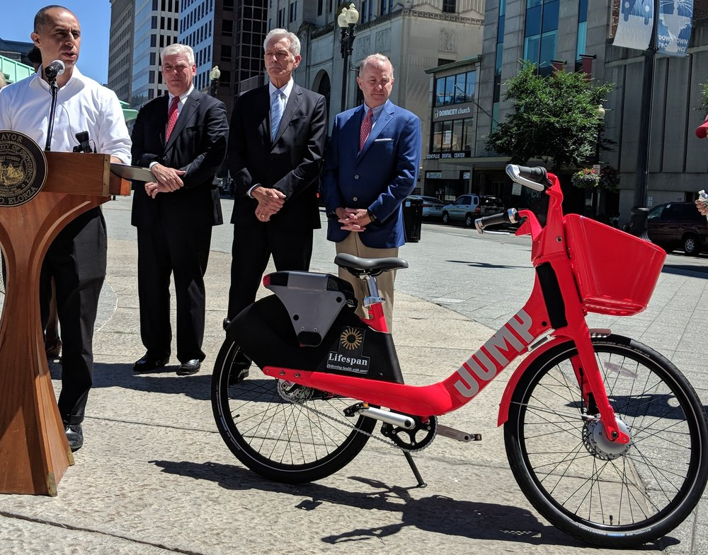 Two health-care companies will sponsor the Providence bike-share program. Lifespan CEO Timothy Babineau, right, and Tufts Health Plan CEO Tom Croswell, second from right, joined Mayor Jorge Elorza, left, and RIPTA CEO Scott Avedisian at the July 19 announcement. (Tim Faulkner/ecoRI News)