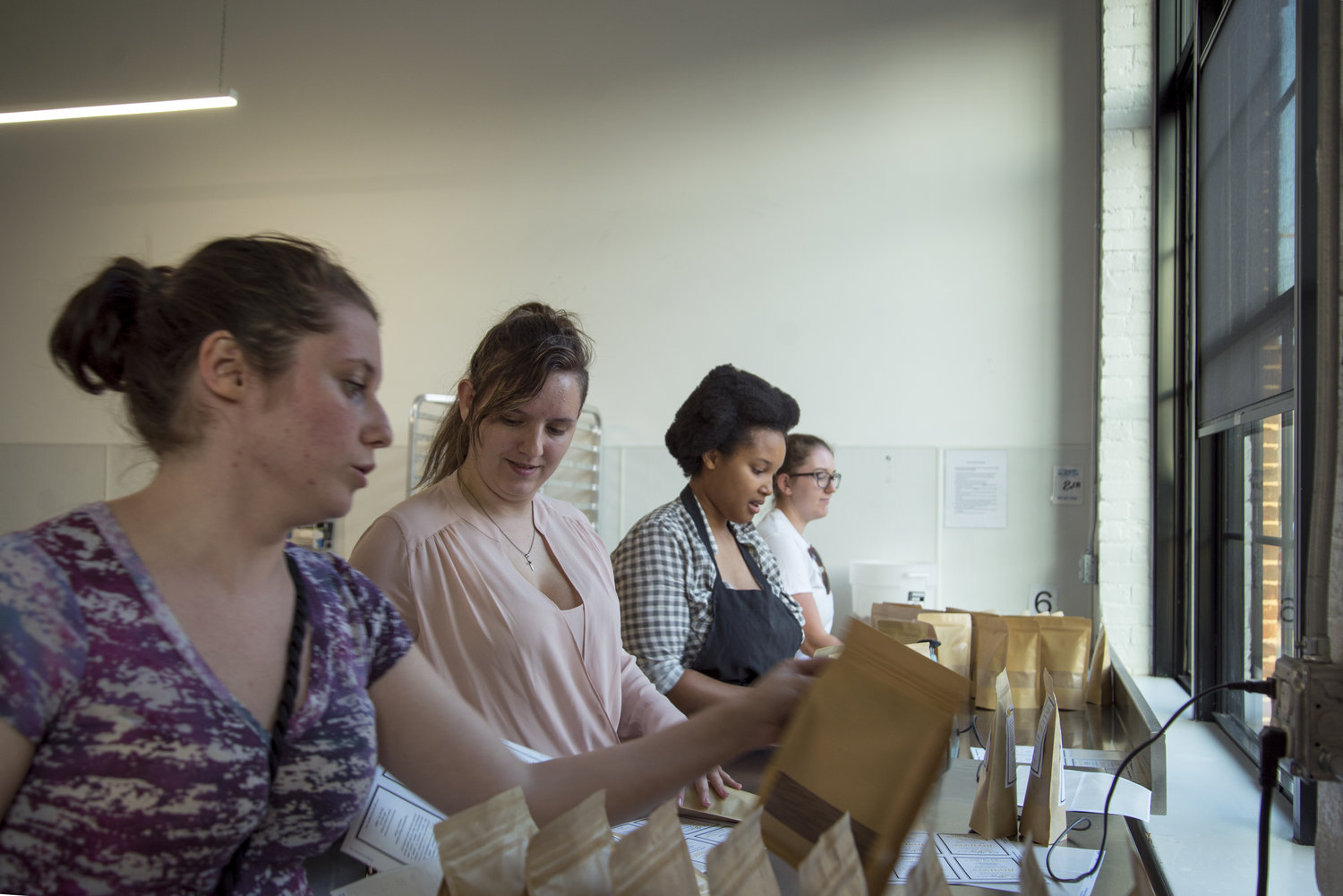 From left, Sam Gannon, Jessie Pulling, Natasha Daniels, and Nicole Gresko work, assembly-line style, to pack and label OURgrain flour, which is made from brewers' spent grain. (Joanna Detz/ecoRI News)