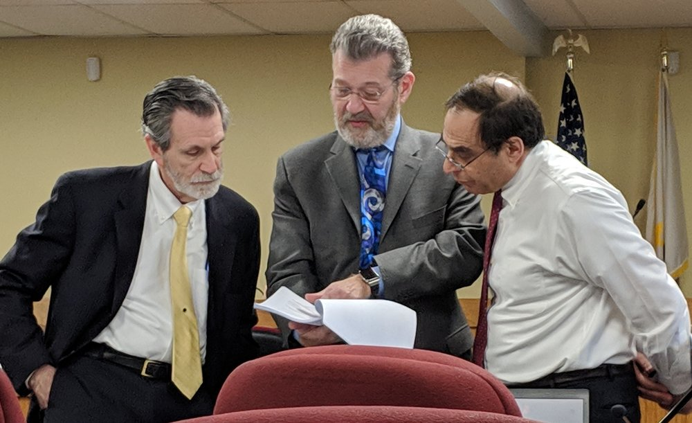 Attorneys review documents before the start of the Jan. 8 hearing of the Energy Facility Siting Board. Front left are Michael McElroy, town of Burrillville, Michael Blazer, Invenergy, and Jerry Elmer, Conservation Law Foundation. (Tim Faulkner/ecoRI News)