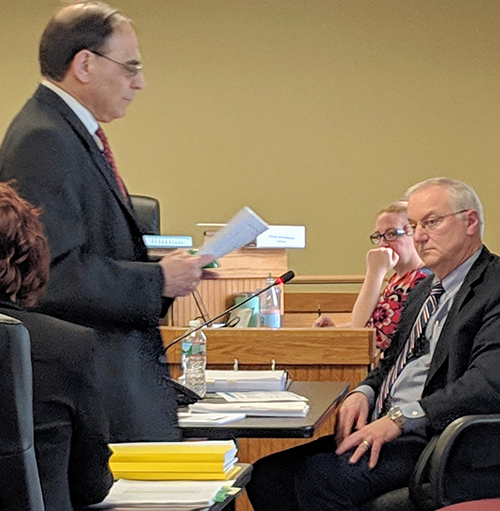Jerry Elmer, left, delivers documents to John Inland during the March 21 hearing of the Energy Facilities Siting Board. (Tim Faulkner/ecoRI News)