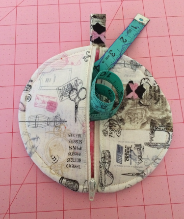 These little circle pouches make great tape measure cozies.  This is done in quilting cotton with a sewing theme print.  I used the method of sewing the pieces right sides together, turning right sides out, and top stitching to finish.