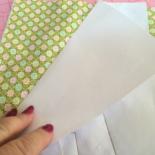 Crease the paper along the stitching.  This will make it easier to tear off the paper.