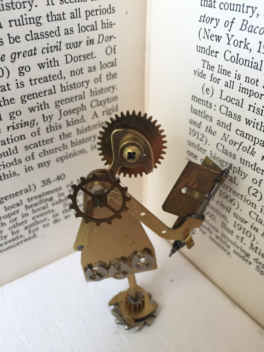 """The Reader."" (4"" x 2"") Metal clockworks and adhesive. (2017) by Melody Weintraub"