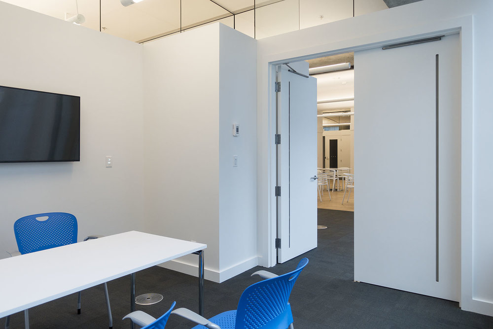 Partial height walls with privacy glass allow natural daylight to penetrate across the floor and maintain acoustic privacy, while VanAir doors exhaust air back to the air returns.