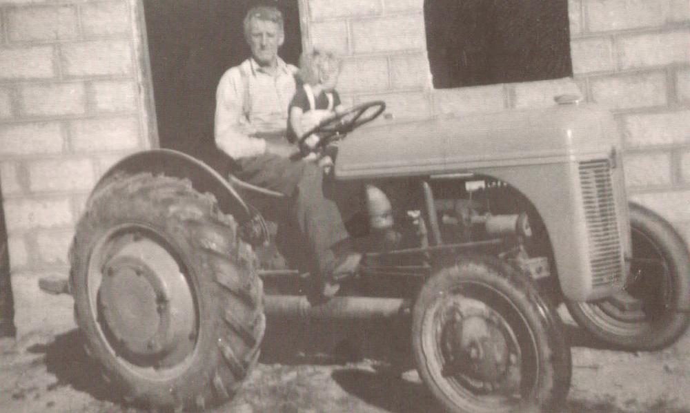 Johannes Kjevik på traktoren med barnebarnet Jan Erik Taraldsen. Bildet er tatt i 1950. Eier av bildet er Ingeborg Taraldsen.