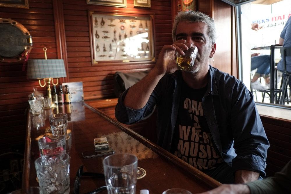 """PÅ STAMPUBEN: Både unge og gamle hevar glaset i ein taus skål til Dimitris, som skåler tilbake. """"Alle"""" kjenner Dimitris."""