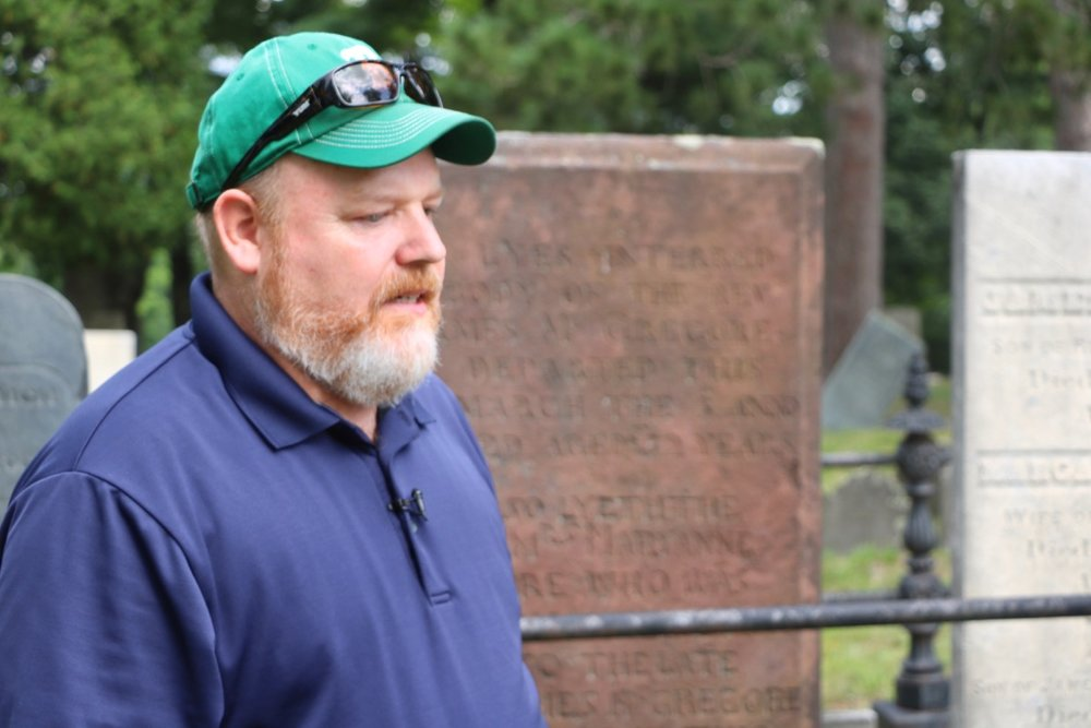 TJ prepares to talk about Rev. James MacGregor in front of the first pastor's deep red sandstone marker.