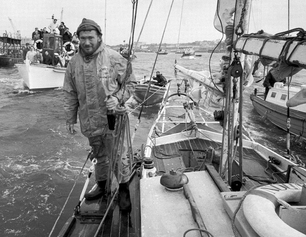 Circa 22nd April 1969- Robin Knox-Johnston with champagne aboard his 32ft yacht Suhaili off Falmouth, England.jpg