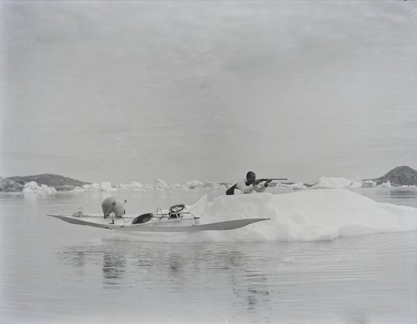 Henry Gino Watkins aiming his rifle as his kayak rests on an ice floe. Greenland, 1930 by Cozens, Henry Iliffe.jpg