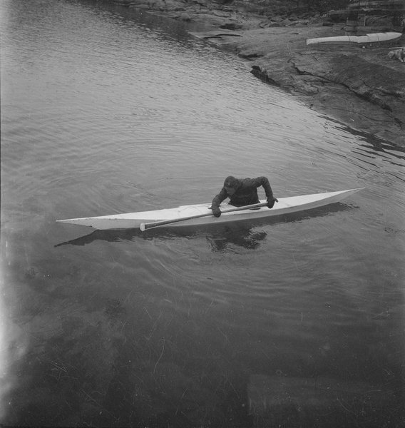 A member of the British Arctic Air Route Expedition 1930-31, sits in a kayak, leaning forward holding his paddle alongside by Frederick Spencer Chapman. Scott Polar Research Institute.jpg