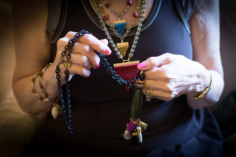 Putting the finishing touches on a long necklace made with a variety of tassels, wood, and Murano glass.