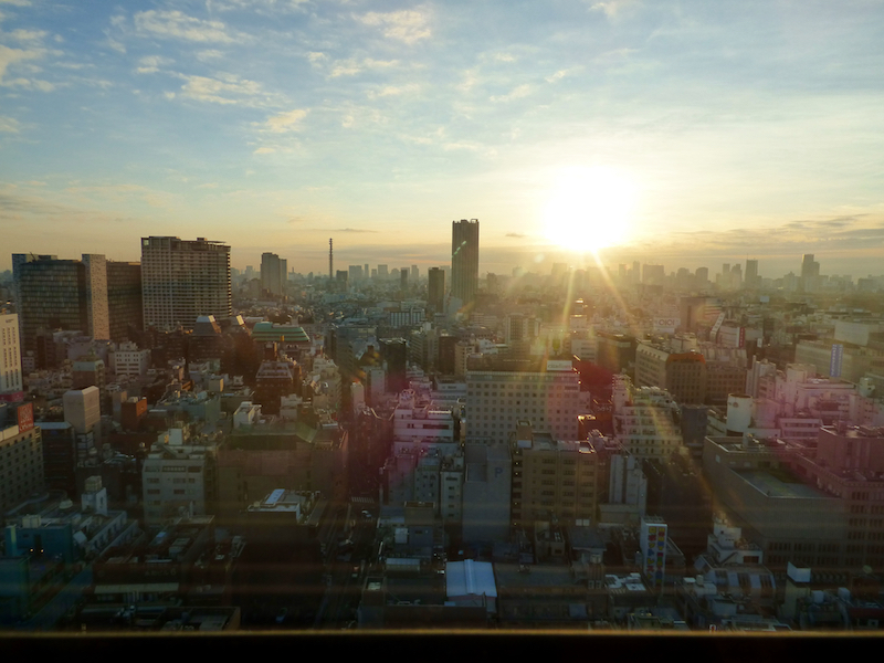 view of the rising sun over tokyo from my shinjuku hotel room..