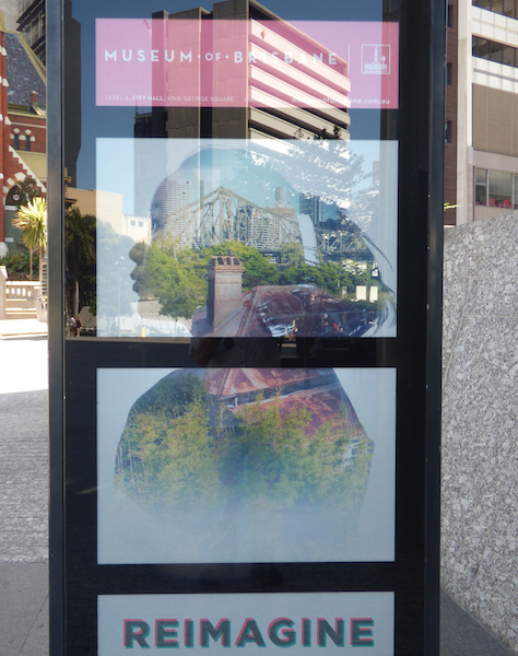 Photo of poster announcing a show at the Brisbane Museum, with glass reflecting the city surroundings taken in Brisbane, Australia in 2014