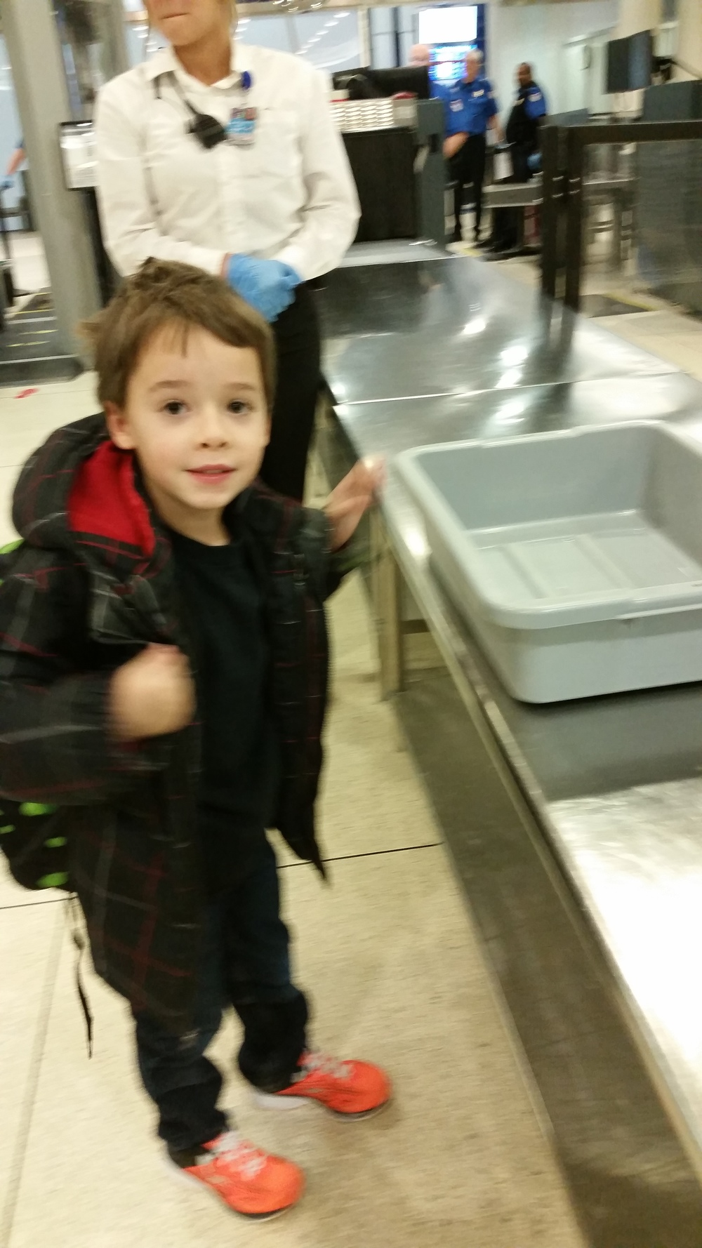 Emerson puts his jacket and backpack in the bin.