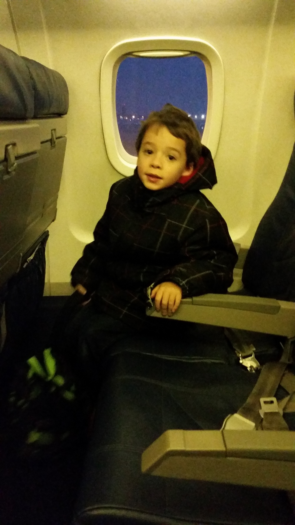 Emerson finds his seat on the airplane.