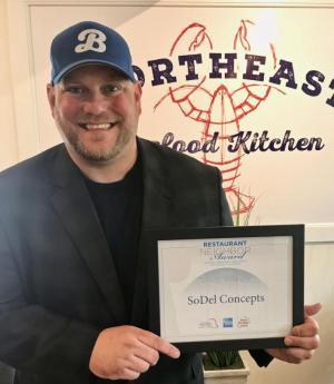 Scott Kammerer, SoDel Concepts president, holds the Restaurant Neighbor Award honoring outstanding community service and involvement.