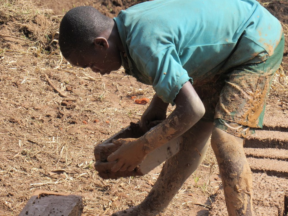Young Ugandan boy in suffering heat making sun dried bricks every day, all day, no relief