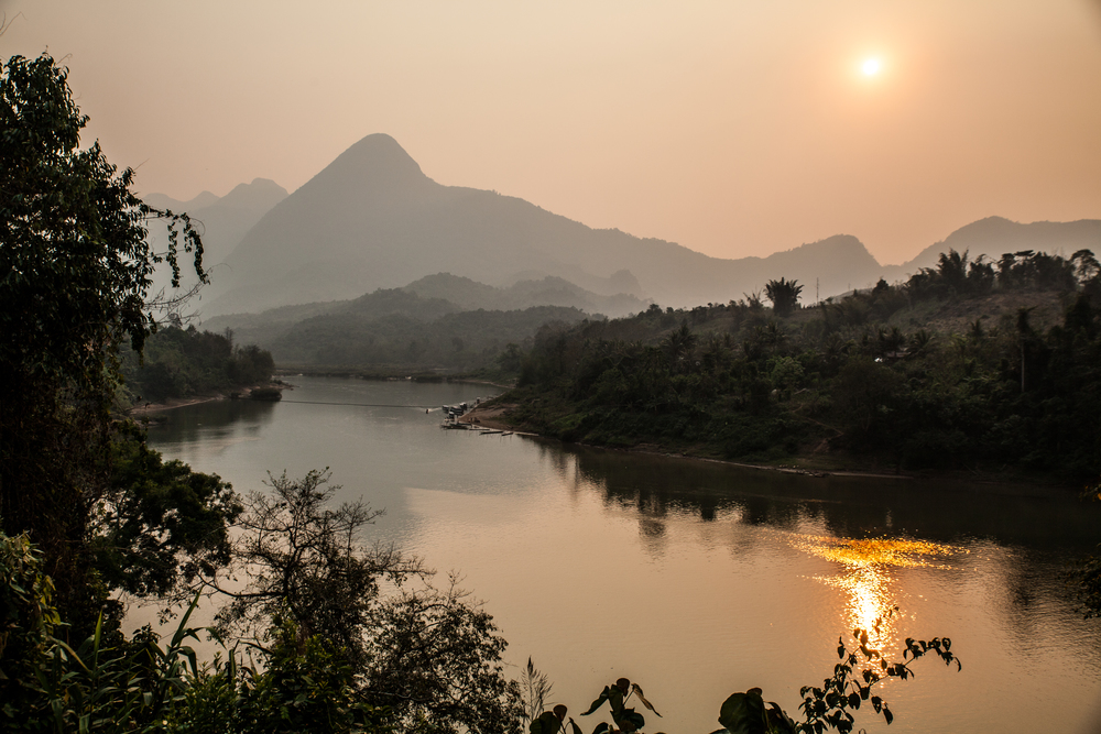 The Nam Ou River and a hazy sunset.