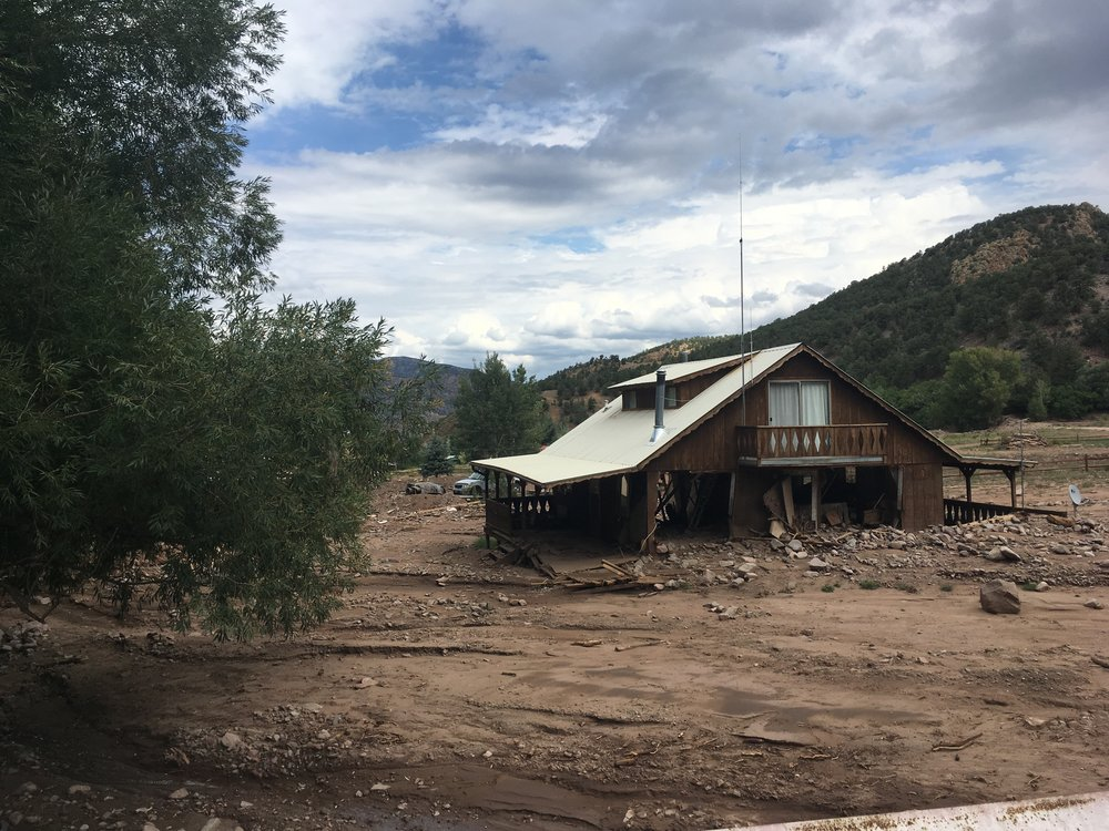 A home near Cotopaxi, Colorado destroyed by water and sediment moving over an alluvial fan. This damage was not associated with a dramatic flood event, rather it was the result of a typical summer thunderstorm that occured over an area burned by a wildfire.