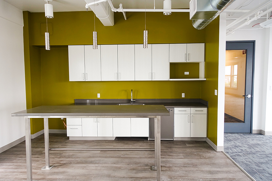 office kitchen, green wall paint, white cabinets, gray table